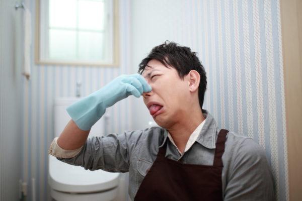 臭いトイレにいる男性